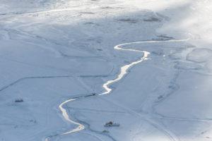 Island aus der Vogelperspektive, Bauernhof an einem Fluss im tiefsten Winter