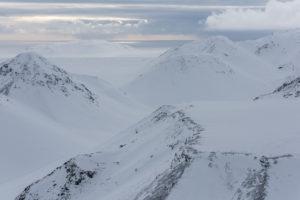 Island aus der Vogelperspektive, unberührter Schnee auf den Bergen, im Hintergrund der Atlantik