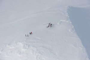 Hubschrauber ist gelandet auf dem schneebedeckten Eyjafjallajökull bei schönstem Winterwetter im Februar, der Pilot und drei Passagiere sind ausgestiegen