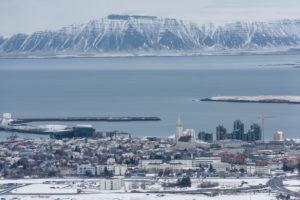 Zentrum Reykjavik aus einer Cessna fotografiert, Hallgrímskirkja und Harpa sind deutlich sichtbar, im Hintergrund das Esja Gebirge
