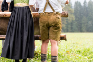 Viehscheid' after alpine pasture drive in late summer in Bavaria, farmer's wife in Dirndl, farmer in leather trousers, details, back view