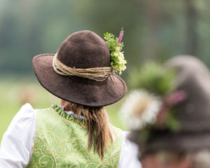 Viehscheid' after the cattle drove down from the mountain pastures in late summer in Bavaria, farmer's wife with felt hat and flower decoration, back view