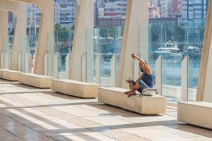 """Ein Tag in Málaga; Impressionen aus dieser Stadt in Andalusien, Spanien. Die wunderschöne moderne Boulevard-Promenade """"El Palmeral de las Sorpresas"""" von Architekt Jerónimo Junquera. Frau macht Selfie."""