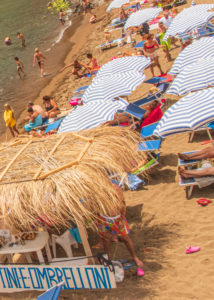Sicily - Sunny impressions of the Aeolian Islands, also known as Aeolian Islands or Isole Eolie: Lipari, Stromboli, Salina, Vulcano, Panarea, Filicudi and Alicudi. Beach life on Panarea: parasol rental on the Zimmari sandy beach.