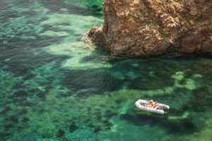 Sicily - Sunny impressions of the Aeolian Islands, also known as Aeolian Islands or Isole Eolie: Lipari, Stromboli, Salina, Vulcano, Panarea, Filicudi and Alicudi. Crystal clear water at Cala Junco, Panarea. Couple in an inflatable boat.