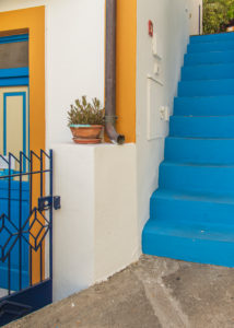 Sicily - Sunny impressions of the Aeolian Islands, also known as Aeolian Islands or Isole Eolie: Lipari, Stromboli, Salina, Vulcano, Panarea, Filicudi and Alicudi. Steep blue concrete stairs next to a colorful front door on Panarea.