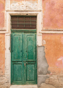 Sicily - Sunny impressions of the Aeolian Islands, also known as Aeolian Islands or Isole Eolie: Lipari, Stromboli, Salina, Vulcano, Panarea, Filicudi and Alicudi. Green wooden door in an old facade on Panarea.