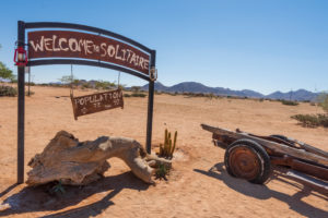 "A jeep tour through Namibia, wildlife, country and people. Sign ""Welcome to Solitaire"" and ""Population"" in Solitaire"