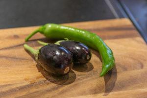 Auberginen ernten und vegetarisch kochen: gesunde und nachhaltige Ernährung aus dem eigenen Garten. Zwei Auberginen und eine grüne Paprika auf einem Holzbrett.