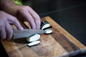 Auberginen ernten und vegetarisch kochen: gesunde und nachhaltige Ernährung aus dem eigenen Garten. Auberginen schneiden mit einem Santoku-Messer.