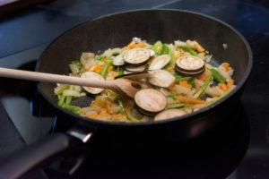 Auberginen ernten und vegetarisch kochen: gesunde und nachhaltige Ernährung aus dem eigenen Garten.  Zubereitung einer Gemüsesoße mit Auberginen.