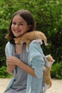 Girl with two kittens on shoulder and back laughs in the camera, trees in the background, blurred