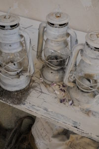 old white lanterns on shabby chic shelf with net and mussels