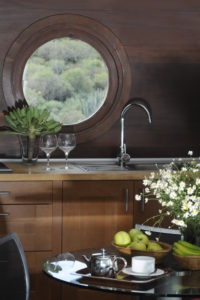 Kitchen with porthole windows in a climate-friendly house in the south