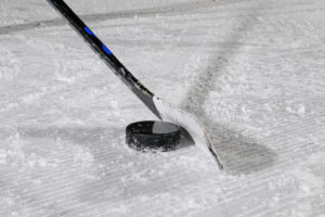 Ice hockey stick and puck on ice surface, close-up