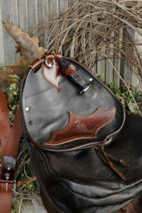Falconer's bag with falconer's knife in front of decoration from dry branches