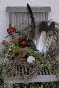 Eagle bonnets and eagle feathers arranged on wooden chair, still life