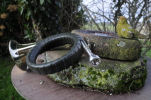 Hunting horn on moss-covered stone beside stone bird bath