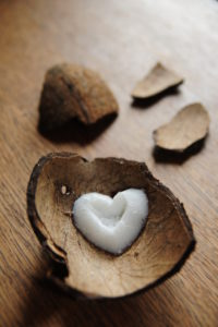 Piece of coconut peel with heart of coconut on dark wood, blurred peels in the background