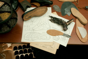 Shoemaker's workshop, drawing for tailor-made shoes, unfinished handcrafted shoe and soles