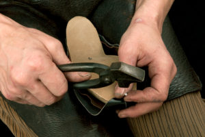 Shoemaker's workshop, shoemaker nailing leather into the wooden model