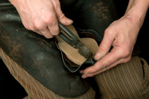 Shoemaker's workshop, shoemaker putting leather over the wooden model with pliers