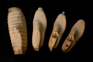 Handmade wooden models in shoemaker's workshop, work piece from rough to fine on black ground