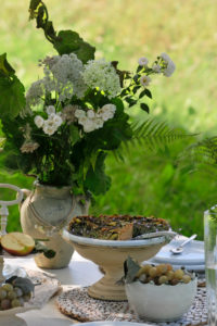 Vegane mangold quiche and white bunch of flowers on laid table, in the background blurred meadow, close up