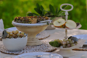 Vegane mangold quiche close thyme, Etagere with sliced apple on white laid table, in the background blurred meadow