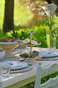 Mangold quiche and Etagere with sliced apple on white laid table, in the background blurred meadow and brook