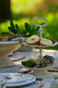 Etagere with sliced apple and grapes on white dining table, in the background blurred summer meadow