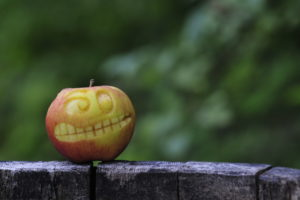 Apple with carved face in front of blurred background, close up