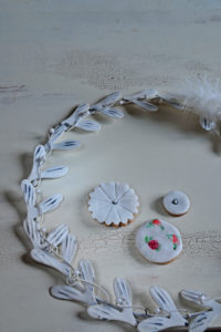 Cookies with white fondant coating surrounded by white metal wreath