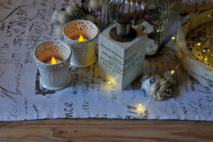 Christmas table decoration in white with artificial candles and fairy lights