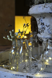 Christmas table decoration, bottles with filigree branches and fairy lights