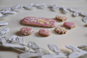 Cookies with pink fondant coating and colorful caster sugar with white metal wreath