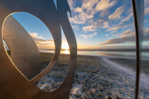 Sunrise on the south beach, sculpture, detail, wave over the wall by Werner Reichhold made of V2A steel, south beach, Wilhelmshaven, Lower Saxony,