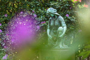 Mourning woman statue, rhododendron blossom, Ohlsdorf cemetery, Hamburg,