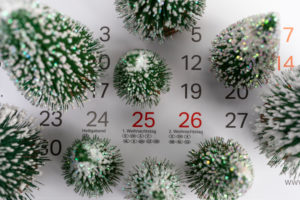 Miniature Christmas trees stand on calendar month of December, appointment calendar, detail, Christmas Eve, symbol picture, Christmas time, appointment reminder,