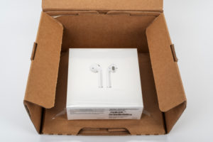 Apple AirPods 2 in shipping box, opened, white background,