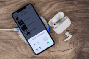 Apple iPhone 11 Pro Max lies on charging pad, display shows charging status of AirPods Pro, wireless charging,