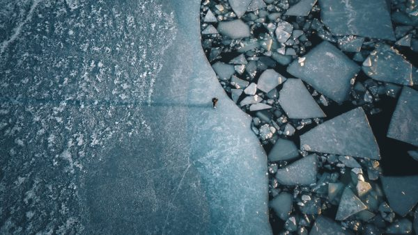 A lonely person on a lip in the Baltic Sea on the coast of Turku, Finland. The ice floes are created by the passage of ferries and ships