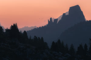 The striking rock formation Cinque Torri at sunrise in front of different layers of mountain ranges and hills in silhouette with a flock of birds