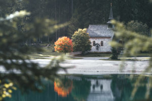 A church on Lake Braies / Pragser Wildsee which is reflected in this lake. Next to the church is a tree with the first red autumn leaves and it stands out. South Tyrol, Dolomites, Italy