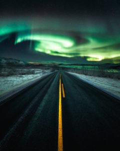 Norldichter across a long straight road near Kilpisjärvi, Lapland, Finland