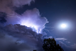 A striking storm cloud from which a lightning bolt emerges with a tree in the foreground and the moon in the clear sky next to it on the island of Sardinia, Italy