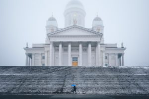 A woman with a blue umbrella in the fog / rain in front of the cathedral in Helsinki, Finland