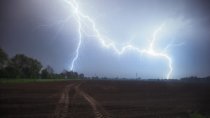 A double lightning strike near Wietmarschen / Nordhorn with a field in the foreground