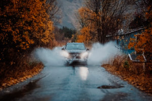 An off-road vehicle drives through a puddle on the island of Senja in Norway in autumn