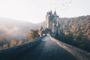 Die Burg Eltz mit einem Vogelschwarm und Nebel im Sonnenaufgang, Herbst, Hunsrück